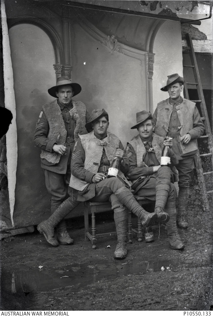 Group portrait of four members of the 13th Australian Light Trench Mortar Battery. The two soldiers in the front row hold bottles of French wine. Identified in this photograph are 3750 Corporal (Cpl) Robert Chaffey Stuart (third from left) and 3489 Private (Pte) John Charles Bitton (fourth from left). Stuart, a labourer from Naracoorte SA, embarked with the 12th Battalion in December 1915, was transferred to the 52nd Battalion in March 1916, and then to the 13th Light Trench Mortar Battery in July of the same year. In January 1919 he was awarded the Meritorious Service Medal. Bitton, a labourer from Maylands WA, embarked with the 28th Battalion in January 1916,